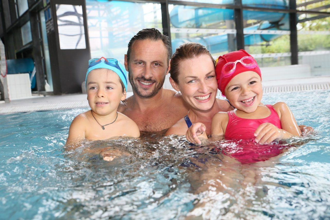 Portrait of family having fun in public indoor swimming-pool